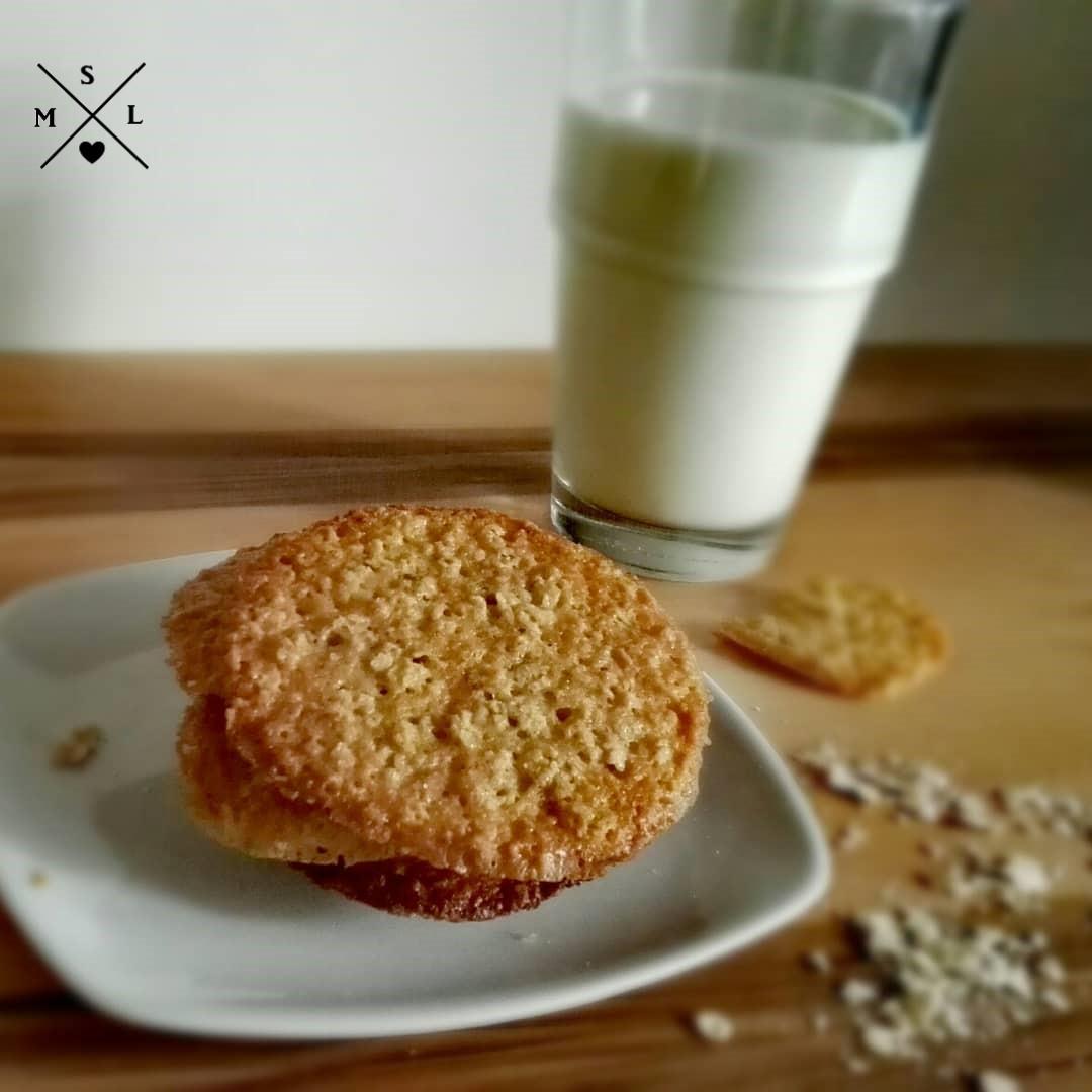 Knusprig gebackener, goldgelber Haferkeks mit einem Glas kalter, frischer Milch